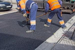Pavage d'asphalte 2 hommes entrain d'étendre de l'asphalte